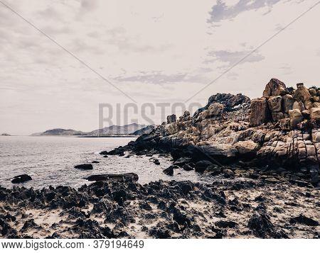 Huge Strange Stone And Sea. Alien Planet Landscape, Rock Formations. Dramatic Toned Photo For Unusua