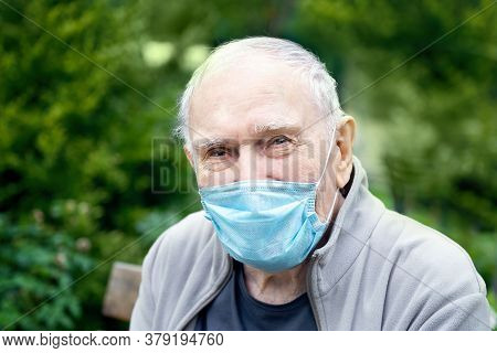 Old Man In A Medical Mask In The Open Air, So As Not To Get Infected With The Virus, Smiles. Prevent