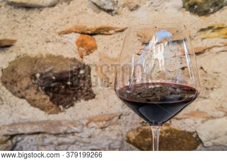 Close-up Of Italian Red Wine In A Glass, Rock Wall On Background. High Quality Photo