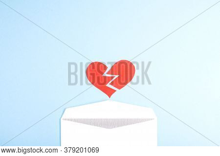 A Torn Red Heart Falls Out Of An Envelope On A Blue Background. Flat Lay, Place For Text