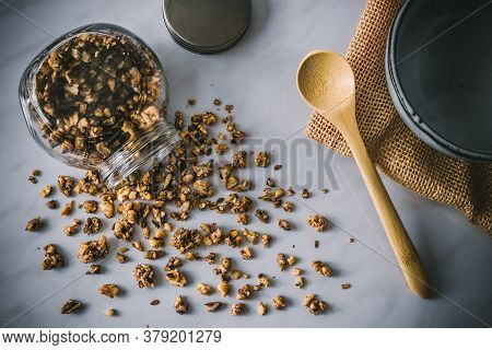 Homemade Healthy And Nutritious Paleo Diet Breakfast Granola In  Glass Jar With Wooden Spoon And Blu
