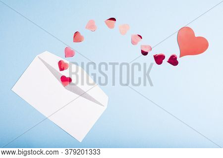 Red Confetti Hearts Fly Out Of A White Envelope On A Light Blue Background. Valentines Day. Love Con