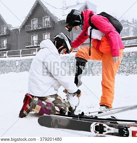 Couple Of Tourists Getting Ready For Skiing In Mountains In Winter. Man Helps His Woman To Put On Sk