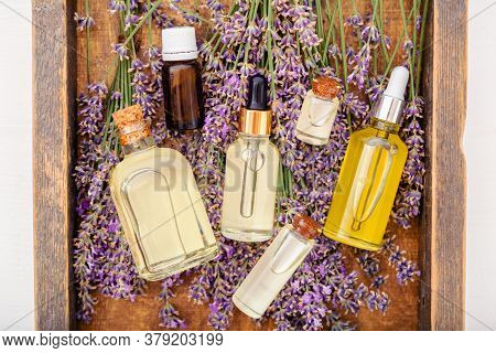 Oil Serum Oils On Lavender Flowers In Brown Wooden Box. Lavender Essential Oil, Serum, Body Butter,