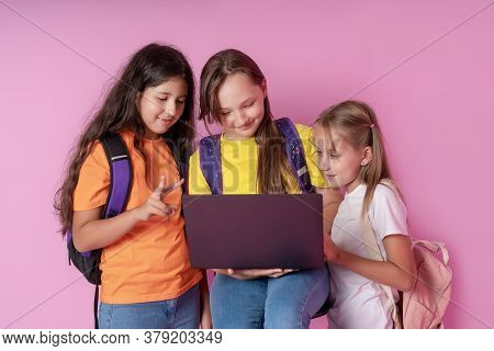 Three Schoolgirls Are Looking At A Laptop With Enthusiasm. Distance Learning Concept