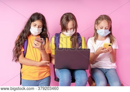 Three Schoolgirls In Medical Masks Are Holding Smartphones And A Laptop. Distance Learning Concept.