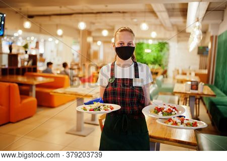 Waiter In Protective Mask Hold Plates With Salad In The Restaurant.