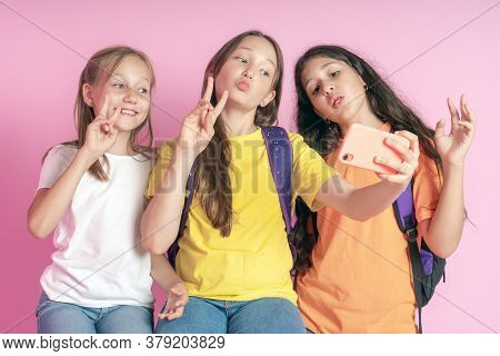 Three Teen Girls Smiling And Shoots A Video On A Pink Background. Selfies