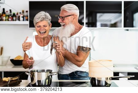Happy Senior Couple Having Fun Cooking Together At Home - Elderly People Preparing Health Lunch In M