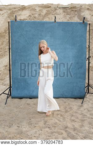 Beauty Portrait Outdoors On Sand In Front Of Blue Studio Background, Pretty Female Posing. Attractiv