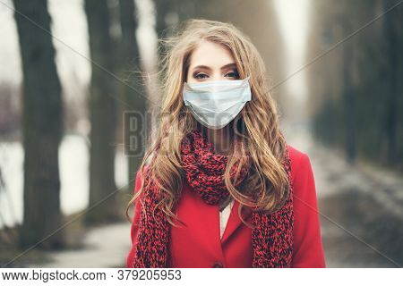 Beautiful Young Woman In Medical Protective Face Mask Walking Outdoors