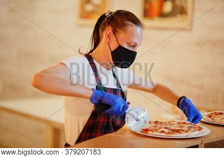Waiter In Protective Mask Cutting Pizza In Pizzeria.