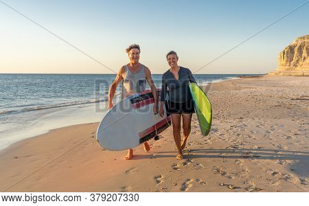 Mature Couple Surfers With Surfboard Having Fun On Empty Remote Beach Enjoying Outdoors Lifestyle