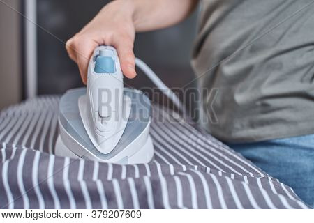 Woman Ironing Clothes On Ironing Board With Modern Iron