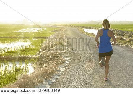 Sunset Backlight Of A Sportswoman With Blue Shirt Running Down A Path Next To A Rice Field