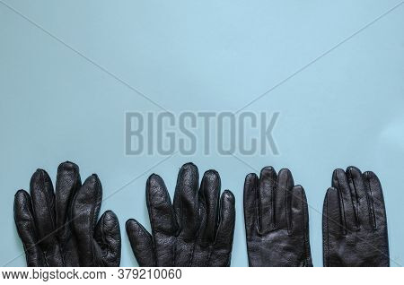 Black Leather Gloves On Light Blue Background. Pair Of Male And Pair Of Female Gloves. Top View At A