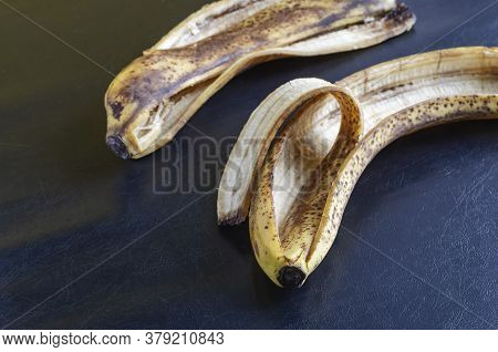 Detailed Photo Discarded Banana Peel On Black Background. The Peel Of Overripe Bananas With Brown Sp