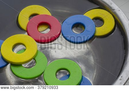 Multi-colored Details Of Childrens Designer Set In Metal Bowl With Water. Cleaning Childrens Toys Fr