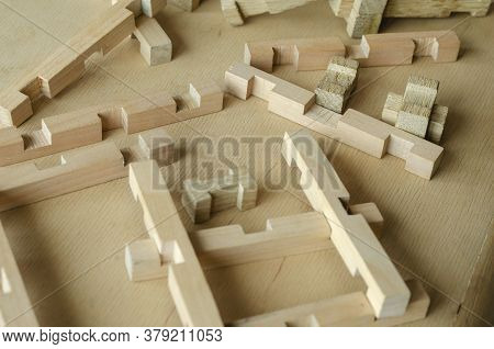 Details Of The Childrens Wooden Constructor Randomly On The Wooden Table. Close-up Of A Developing C