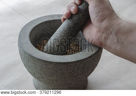 The Hand Of An Adult Caucasian Man Grinds Random Medicinal Roots And Herbs In Stone Mortar. Mixture