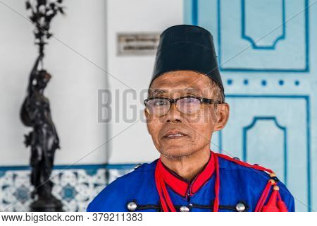 Solo, Indonesia - November, 02, 2017 Guard In Tradional Clothes At The Entrance The Colorful Blue Pa