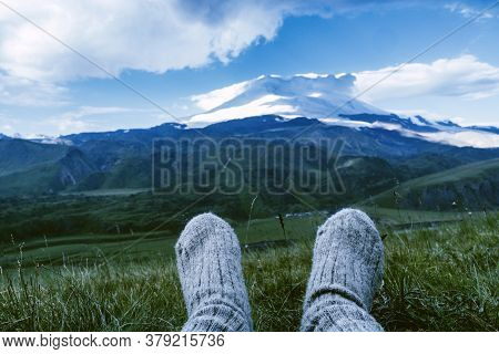 Legs In Knitted Gray Woolen Socks. Morning View On The Caucasus Mountains To Elbrus. Travel Lifestyl