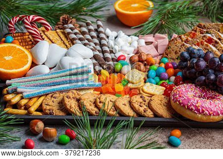 Christmas Sweets Platter. Christmas Fruit Cake, Candy, Chocolate, Candy Cane, Cookies, Fruit On Blac