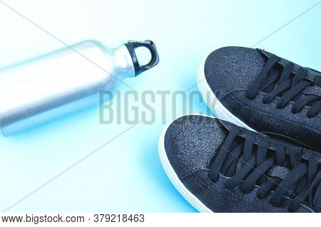 Black Sneakers And Iron Bottle Of Water On Blue Background. Concept Of Healthy Lifestyle, Everyday T