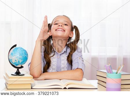 Education And School Concept. Cute Little Student Girl Studying And Raising Hand At School.