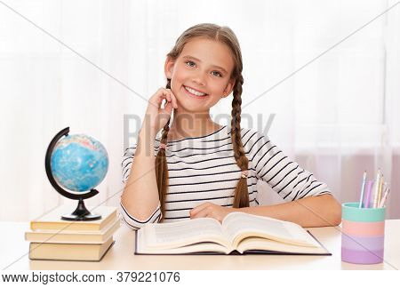 Education And School Concept. Smiling Happy Child Is Sitting At The Desk. Cute Little Student Girl I