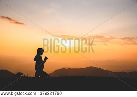 Silhouette Of Christian Woman Praying Worship At Sunset. Christian Religion Concept Background. Hand