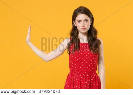 Young Brunette Woman Girl In Red Summer Dress Posing Isolated On Yellow Background Studio Portrait.