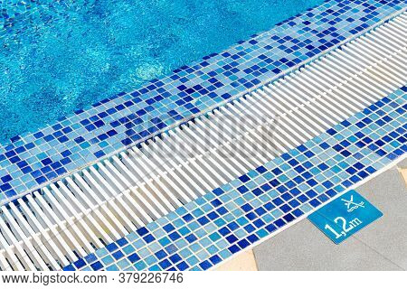 Edge Of Pool With Indication Of Depth Of 1.2 Meters And Sign That Prohibits Jumping