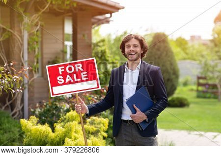 Happy Real Estate Agent Holding For Sale Sign Near Residential Building Outside
