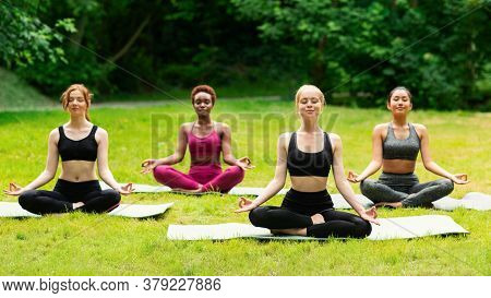 Outdoor Yoga Class. Group Of Diverse Girls Doing Breathing Exercises Or Meditation In Nature. Panora