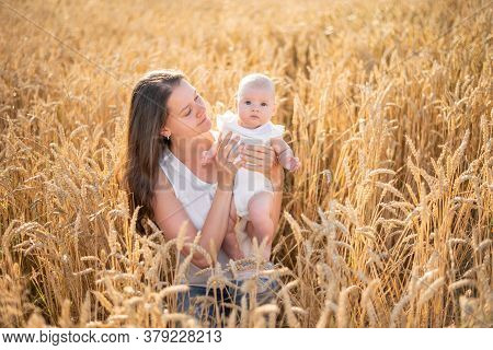 Beautiful Young Mother And Her Daughter Baby Girl At The Wheat Field In Sunny Day In Czech Republic