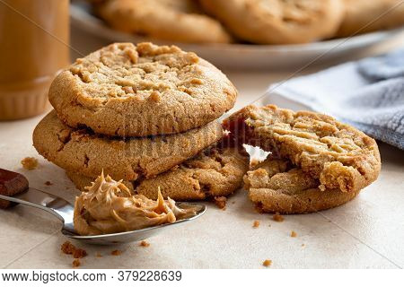 Peanut Butter Cookies On A Table With Peanut Butter Jar And Plate Of Cookies In Background
