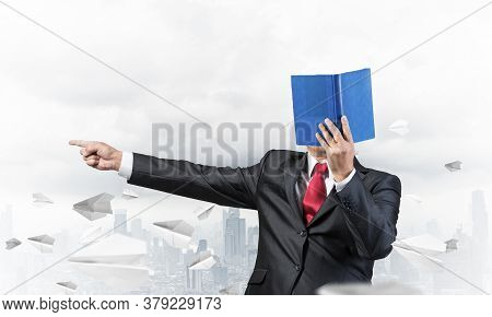Businessman Covered His Face With Organizer And Finger Pointing Side. Man In Business Suit And Tie S