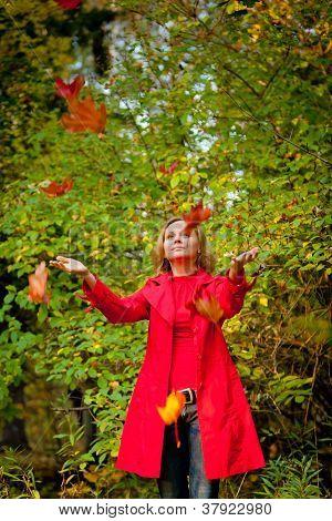 glücklich fallen Frau spielt mit Herbstlaub im Wald