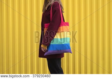 Unknown Woman In Burgundy Coat And Holds In Her Shoulder Rainbow Textile Shopping Bag Against The Ba