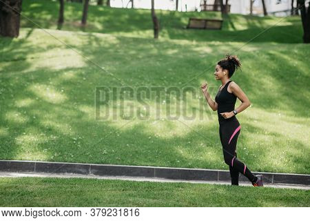 Jogging In Park. Smiling Fit African American Woman With Wireless Headphones And Fitness Tracker Jog