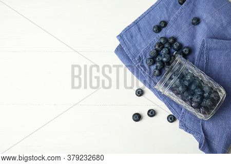 Overturned Glass Jar Of Ripe Blueberries On White Wooden Table, Flat Lay. Space For Text
