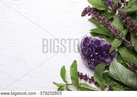 Amethyst Gemstone And Healing Herbs On White Wooden Table, Space For Text