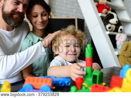 Young Family Spends Time In Playroom. Mom, Dad And Boy
