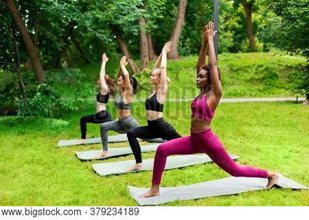 Multinational Young Girls Practicing Yoga Outdoors, Standing In Warrior Pose At Park. Copy Space