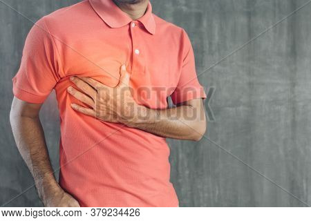 Young Man Holding His Chest In Chest Pain On Cement Wall Background , Problems And Health Care Conce