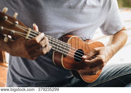 Close Up Young Man Hands Playing Ukulele Guitar