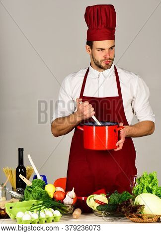 Chef With Tricky Face Holds Red Saucepan On Grey Background.