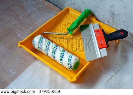 Tools For Plastering Walls. Repair Tools Lies On Floor Of Room Being Repaired.