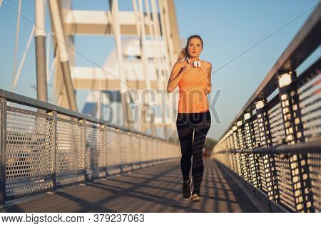 Young Woman Is Jogging Outdoor On Bridge In The City.